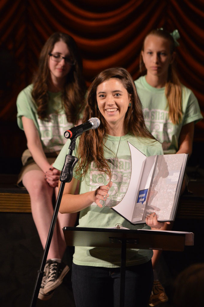 Editor-In-Chief Michela Diddle unveils the 2014 Secondary Yearbook