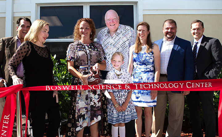 group of people cutting the ribbon for the Boswell Science & Technology Center