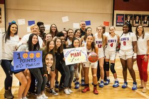 Madison Lee's 1000-point milestone celebrated by teammates and coaches.